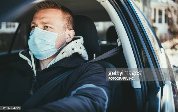 covid-19, young man wearing disposable face mask while driving - driving mask stock pictures, royalty-free photos & images