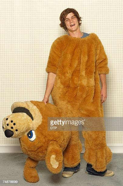 young man wearing dog costume, smiling, portrait - animal costume stock pictures, royalty-free photos & images