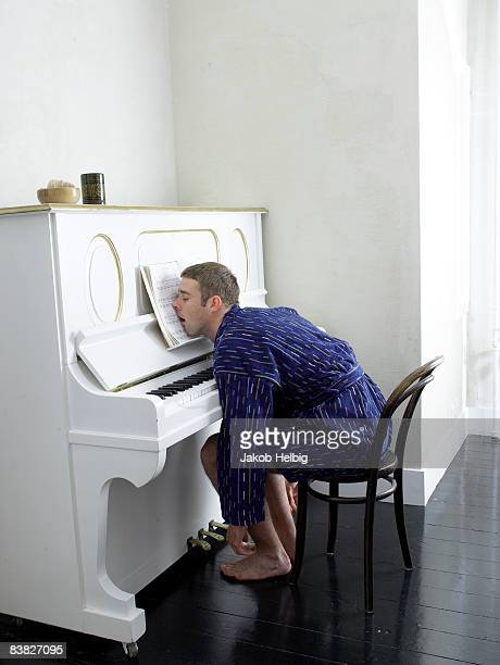 young man wearing dressing gown, playing piano - dormir humour photos et images de collection