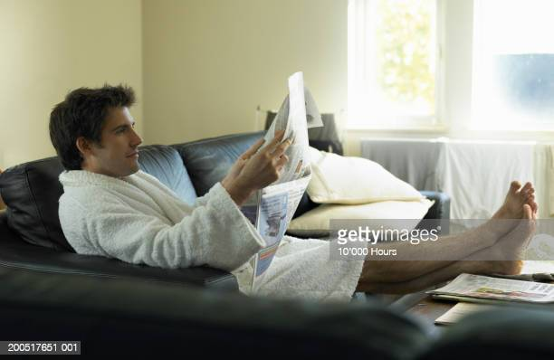 Young man wearing dressing gown relaxing on sofa with newspaper