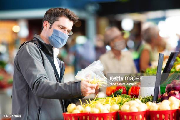 young man wearing face cover selecting string beans at farmer's market - traditionally canadian stock pictures, royalty-free photos & images