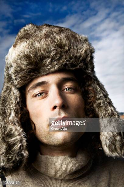 Young Man Wearing Furry Winter Hat Outside Against Blue Sky