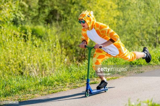 young man wearing giraffe costume on scooter - nur erwachsene stock-fotos und bilder