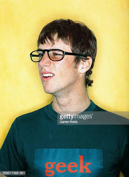 young man wearing glasses and 'geek' t-shirt, close-up - sólo con adultos fotografías e imágenes de stock