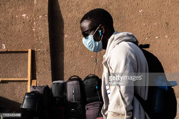 Young man wearing gloves and a face mask in the streets of Dakar, Senegal, on March 6, 2020. Four people have been tested positive to the...