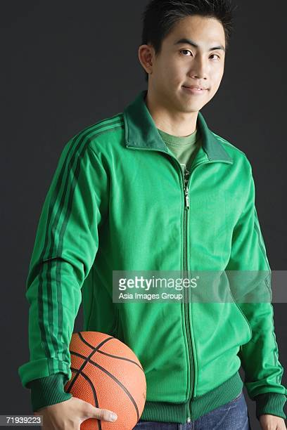 Young man wearing green tracksuit jacket, holding basketball, looking at camera