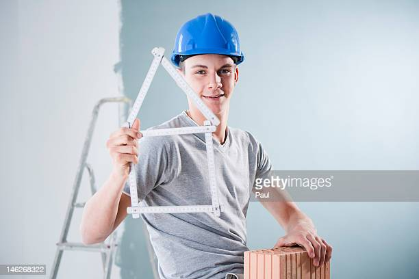 Young man wearing hard hat holding brick and folding rule in shape of a model house