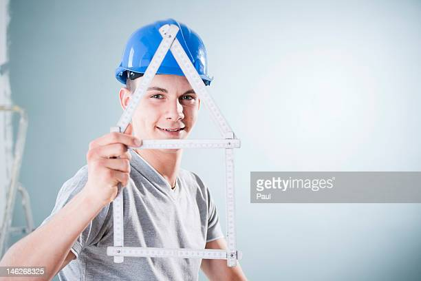 Young man wearing hard hat holding folding rule in shape of a model house