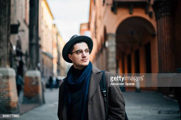 Young man wearing hat and eyeglasses exploring Bologna, Italy