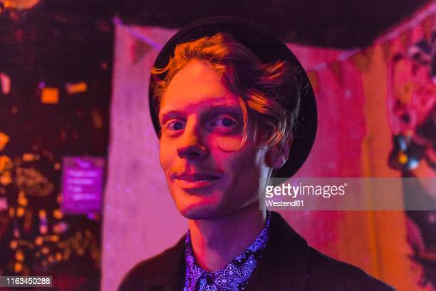 young man wearing hat during psychedelic party, effects of light machine on a wall - alternative lifestyle stock pictures, royalty-free photos & images