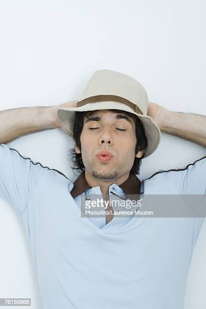 'Young man wearing hat, eyes closed, whistling'