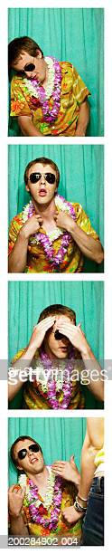 Young man wearing Hawaiian shirt and leis in photo booth