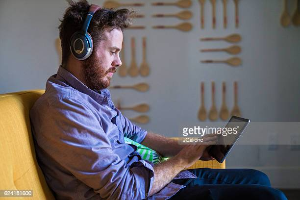 Young man wearing headphones and using a digital tablet
