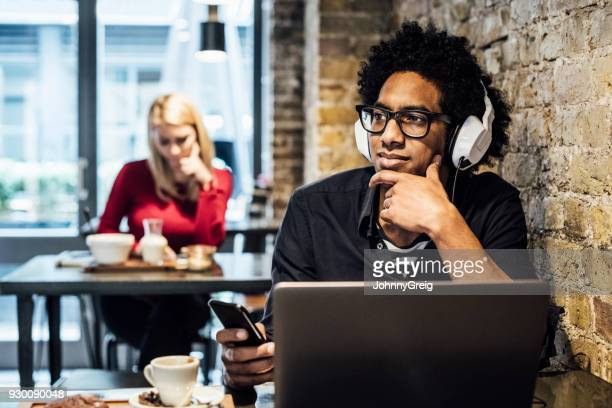 Young man wearing headphones in cafe with laptop and smartphone