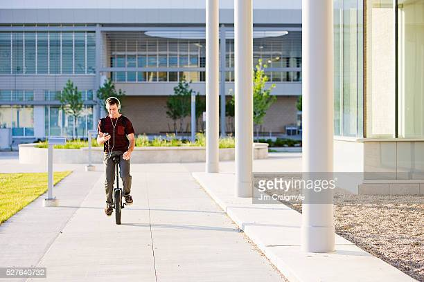 Young man wearing headphones riding monocycle