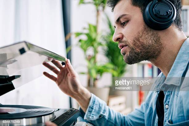 Young man wearing headphones starting record player