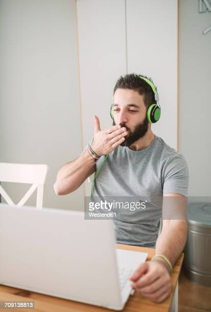 young man wearing headphones, using laptop and blowing a kiss - long distance relationship stock pictures, royalty-free photos & images