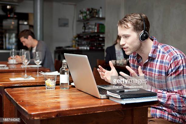 Young man wearing headphones using laptop in cafe