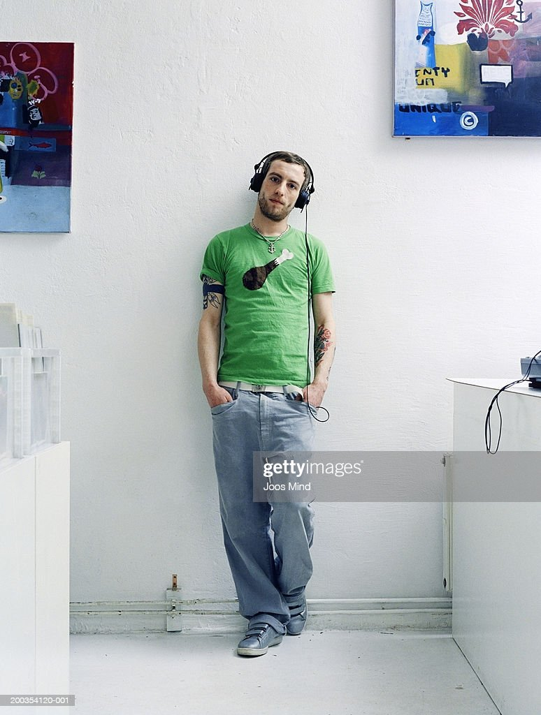 Young man wearing headphones with hands in pockets, portrait : Stockfoto