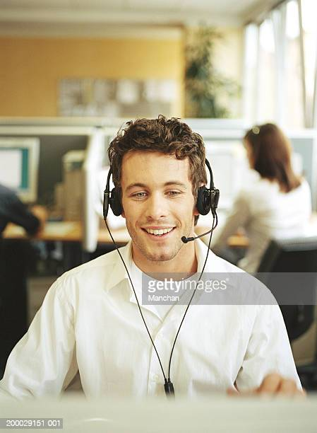 Young man wearing headset in office, smiling