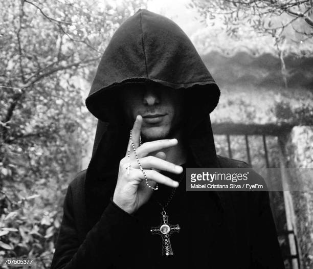 Young Man Wearing Hood Holding Rosary Beads