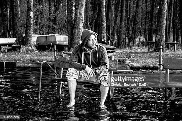Young Man Wearing Hooded Shirt Sitting On Bench Amidst Shallow Water