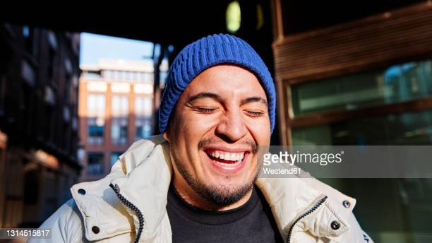 young man wearing knit hat laughing during sunny day - human face stock pictures, royalty-free photos & images