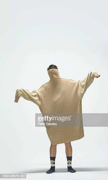 young man wearing large jumper over head and body, arms outstretched - extra groot stockfoto's en -beelden