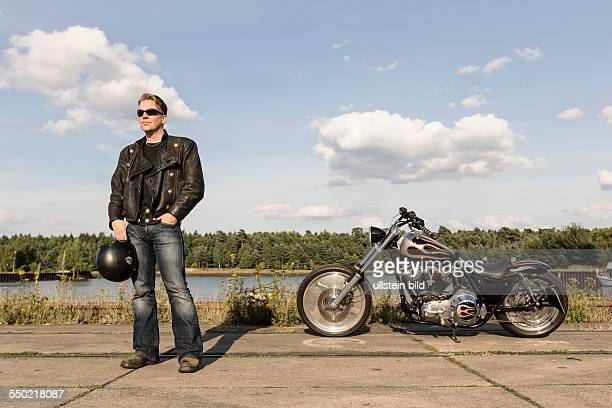 Young man wearing leather clothes with his Harley Davidson