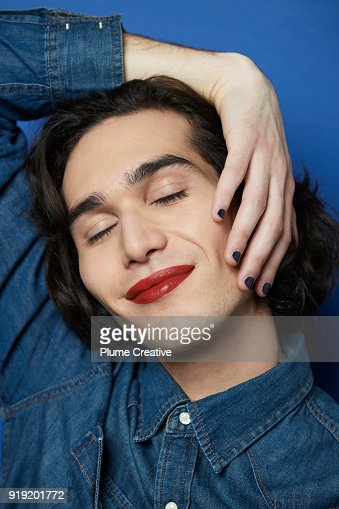 Young Man wearing lipstick with hand on face