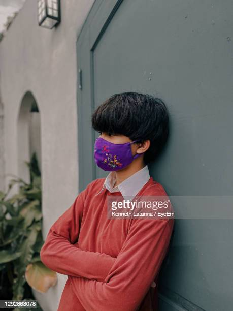 young man wearing mask standing against wall - indianapolis stock pictures, royalty-free photos & images