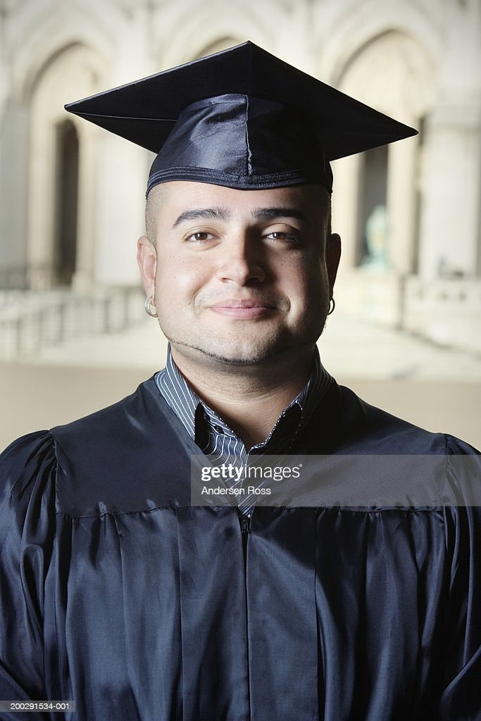 Young Man Wearing Mortar Board And Graduation Gown Portrait Photo
