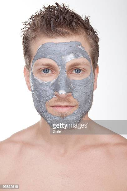 Young man wearing mud face mask