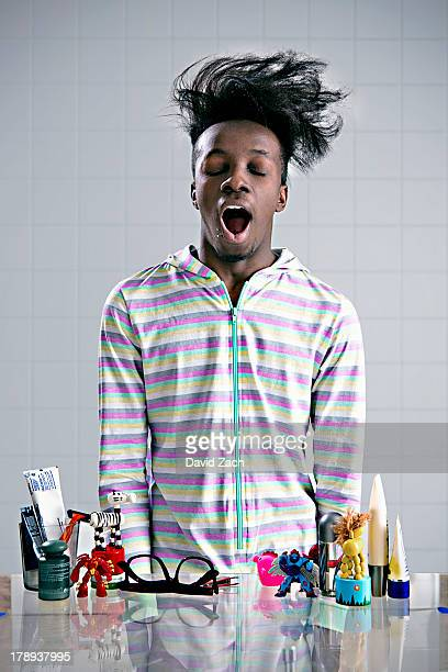 young man wearing onesie, yawning - yawning stock pictures, royalty-free photos & images