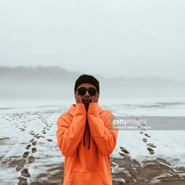 Young Man Wearing Orange Hooded Jacket Standing On Snow Covered Field