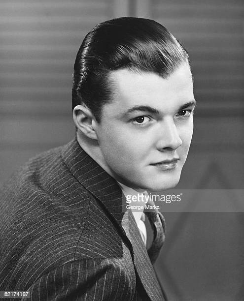Young man wearing pinstripe jacket, (B&W), portrait