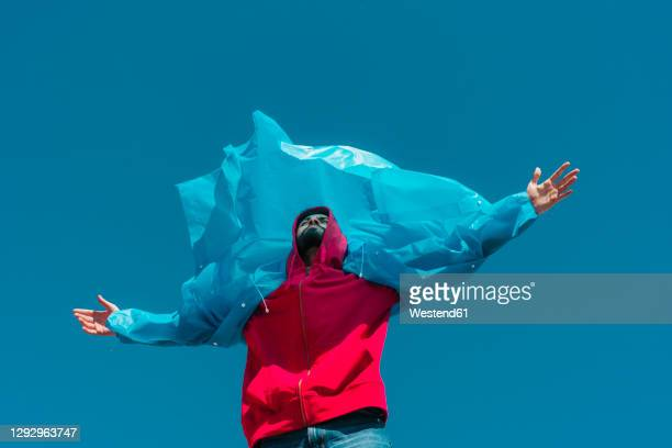 young man wearing plastic rain coat, stanind in gthe wind with arms outstretched - insurrection stock pictures, royalty-free photos & images