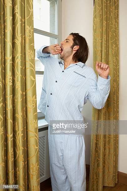 young man wearing pyjamas standing stretching and yawning