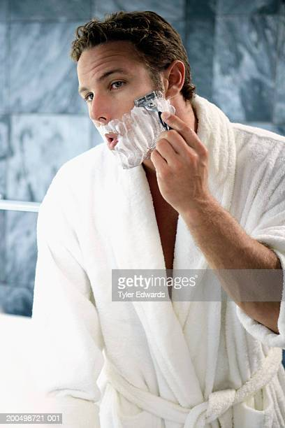 Young man wearing robe shaving in bathroom mirror