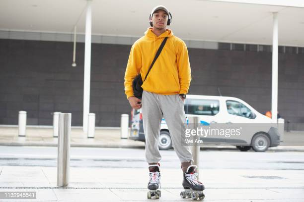 young man wearing roller skates on city street. - sweatshirt stock pictures, royalty-free photos & images