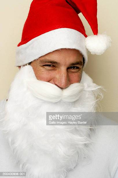 Young man wearing Santa hat and beard, portrait, close-up