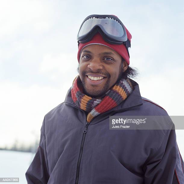 Young man wearing ski goggles on cap, portrait