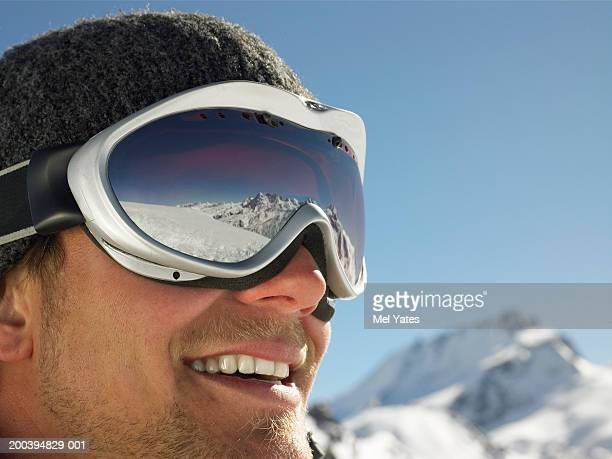 Young man wearing ski goggles on snow field, smiling, close-up