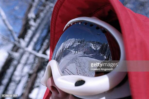 Young man wearing ski goggles, skiers reflected in visor, close-up