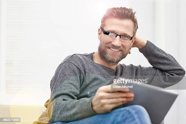 Young man wearing smart glasses with tablet at home