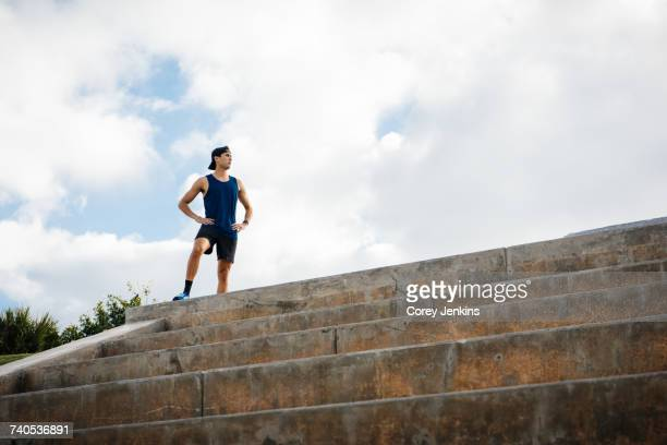 Young man wearing sports clothing, standing at top of steps, hands on hips, South Point Park, Miami Beach, Florida, USA