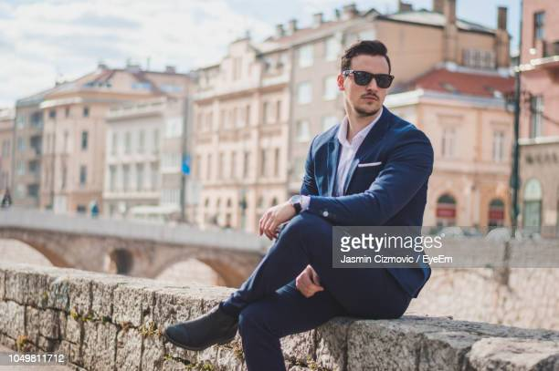 Young Man Wearing Suit And Sunglasses Sitting On Retaining Wall In City