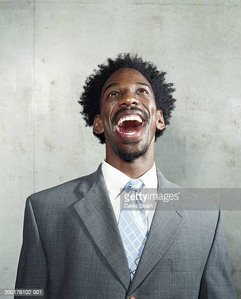 Young man wearing suit, laughing, looking up