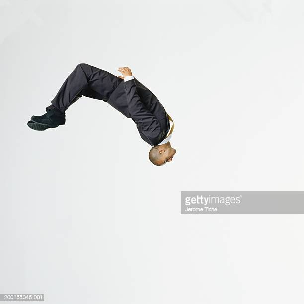 Young man wearing suit performing backflip, side view