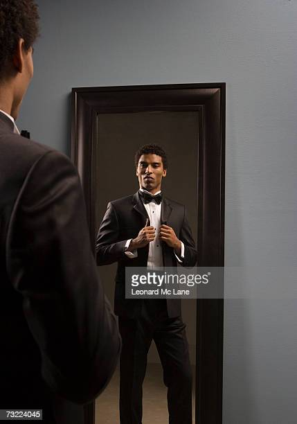 Young man wearing suit, standing in front of mirror